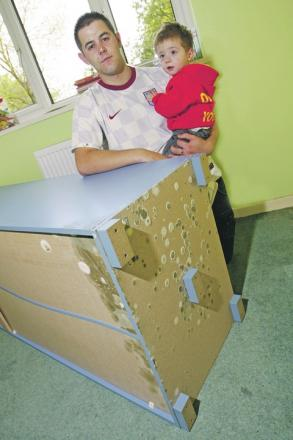 Jason Smith, with son Leo, shows the mould trouble in their Droitwich home.