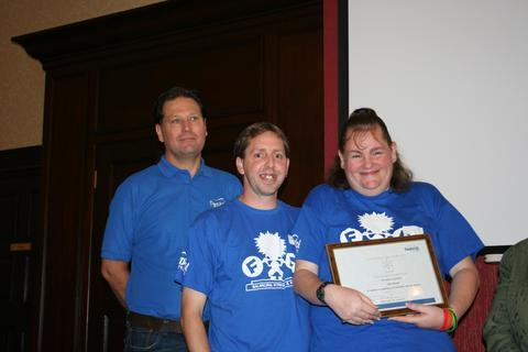 Claire Bowen and her husband receiving the award from Guy Weston, chief executive of Festival Housing.