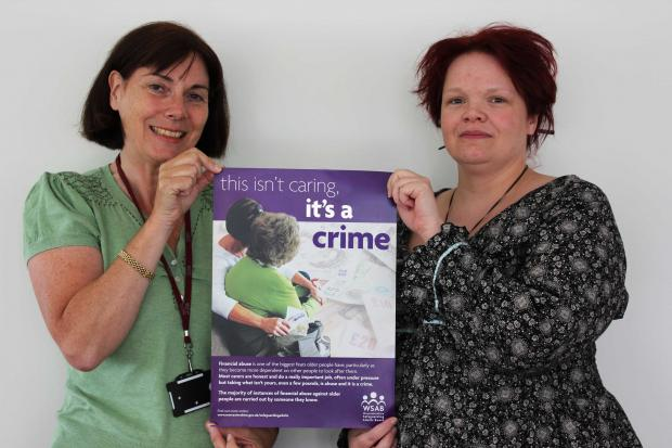Droitwich Advertiser: Sue Pidduck, Worcestershire County Council's Safeguarding Services Manager, and Sarah Pilkington, Worcestershire County Council's Learning and Development Co-ordinator – Adult Protection, unveil the 'This isn't caring, it's a crime' poster
