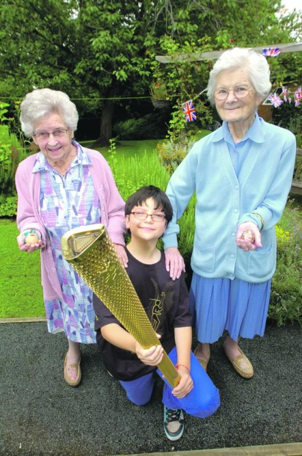 Droitwich Advertiser: Residents Gladys Paish and Joyce Mantle with torchbearer Jack Griffiths, 11.