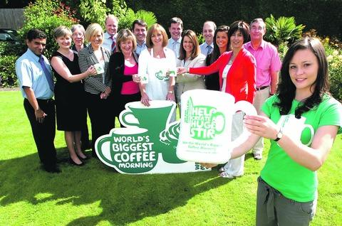 A cuppa for charity: Jo Lucas, a Macmillan volunteer, with consultants, nurses and staff from The Joint Clinic in Droitwich. Buy this photo BMM381202a