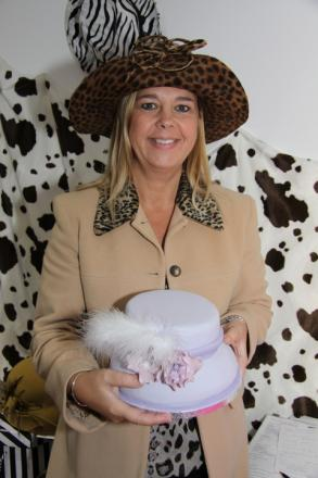 Milliner Caroline Butcher with the hat shaped cake she was presented with at the launch of The Wild Collection.
