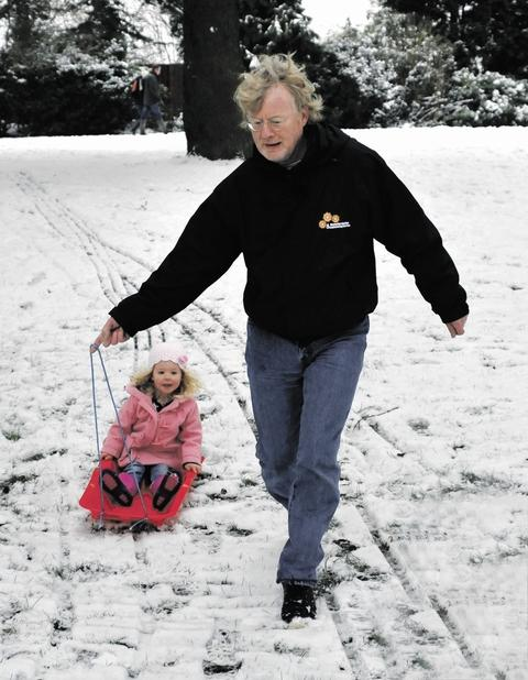 HITCHING A RIDE: Ronnie Moore having some fun with his three-year-old granddaughter Millie on her sledge at Lido Park, Droitwich.