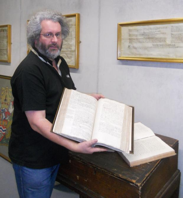 Adrian Gregson, Archival Manager at The Hive, holding the17th century Habington Manuscript – the first history of Worcestershire.