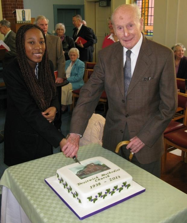 Droitwich Advertiser: Ti Mbatha, one of the newest members of the church, cuts the anniversary cake with oldest member Ivor Wilkinson.