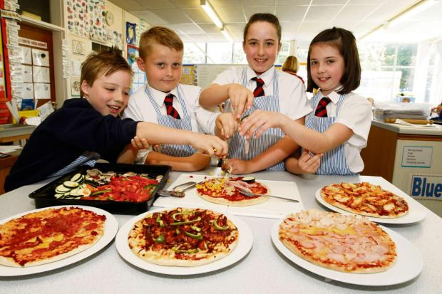 Droitwich Advertiser: Year five pupils Joe Dallaway, Jake Andrews, Anna Smith and Leila Whitehouse at Westacre Middle School design and make their own pizzas. Buy photo: BCR251404_01 at droitwichadvertiser.co.uk/pictures or call 01384 358200.