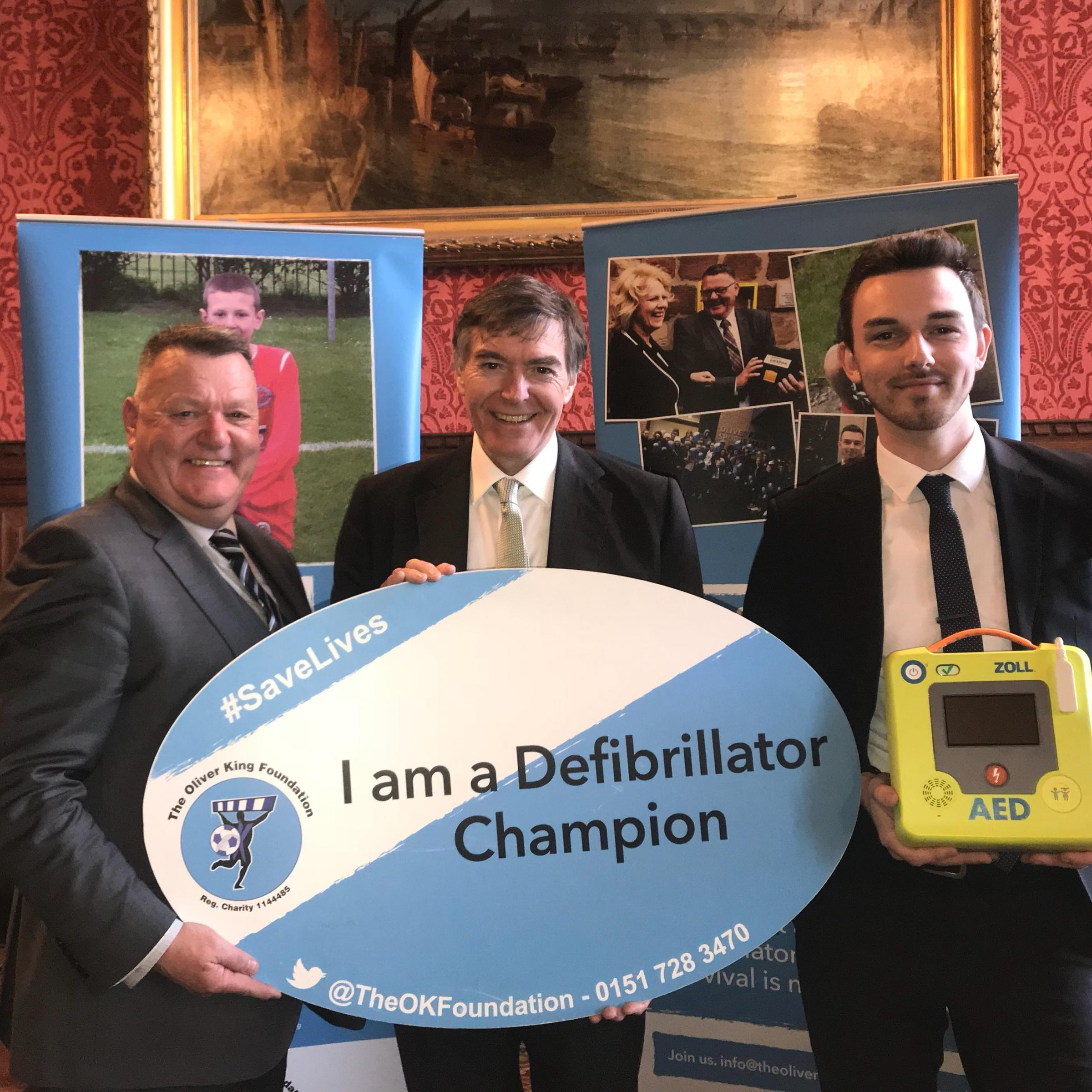 Philip Dunne MP (centre) becomes a defibrilator champion